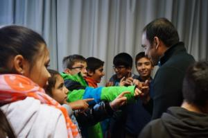 Rais speaking with refugee children, who wanted to feel the bullet fragments under his skin, from Syria, Iraq, and Afghanistan during an annual speaking tour for the Community of Sant'Egidio, Wurzburg, Germany, 2016